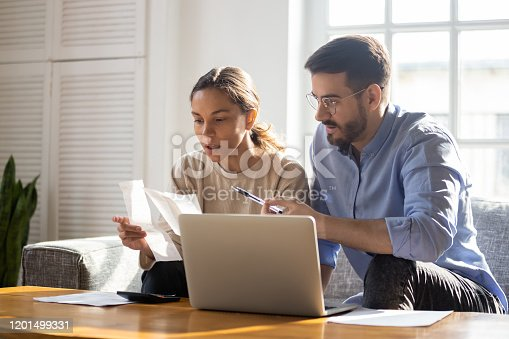 Concentrated young couple sit on couch busy managing finances paying bills on computer online, focused anxious millennial husband and wife calculate household expenses or taxes use internet banking