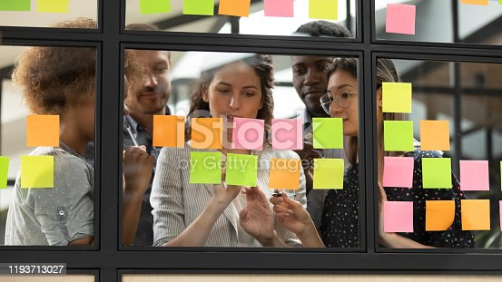 1144569896 istock photo Focused young diverse teammates working with caucasian team leader. 1193713027