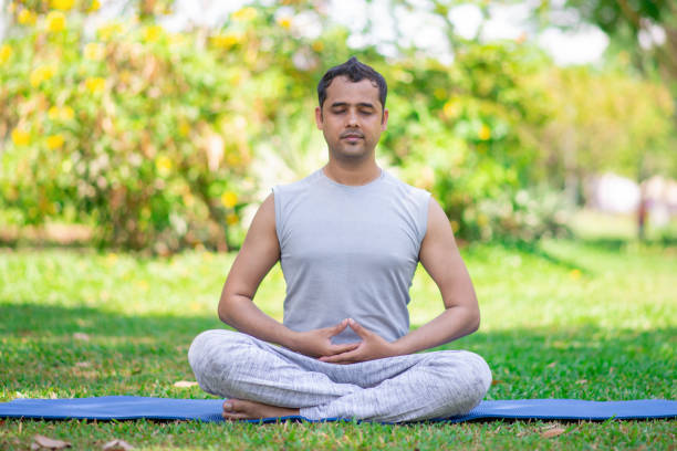 Focused young Indian man meditating in lotus pose Focused young Indian man meditating in lotus pose. Calm young yogi practicing lesson outdoors in park. Yoga and fitness concept lotus position stock pictures, royalty-free photos & images
