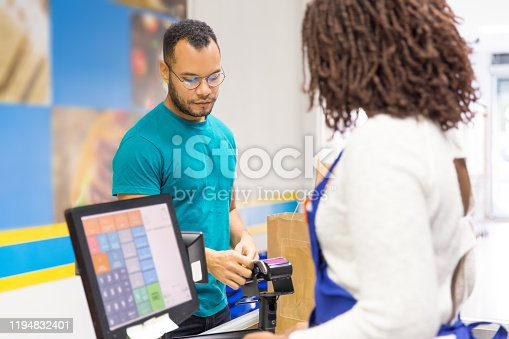 istock Focused young man paying bill in store 1194832401