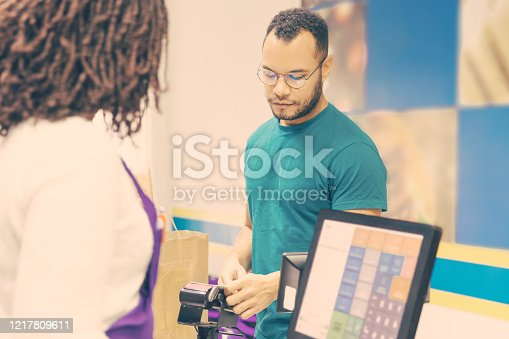 istock Focused young man paying bill in store 1217809611