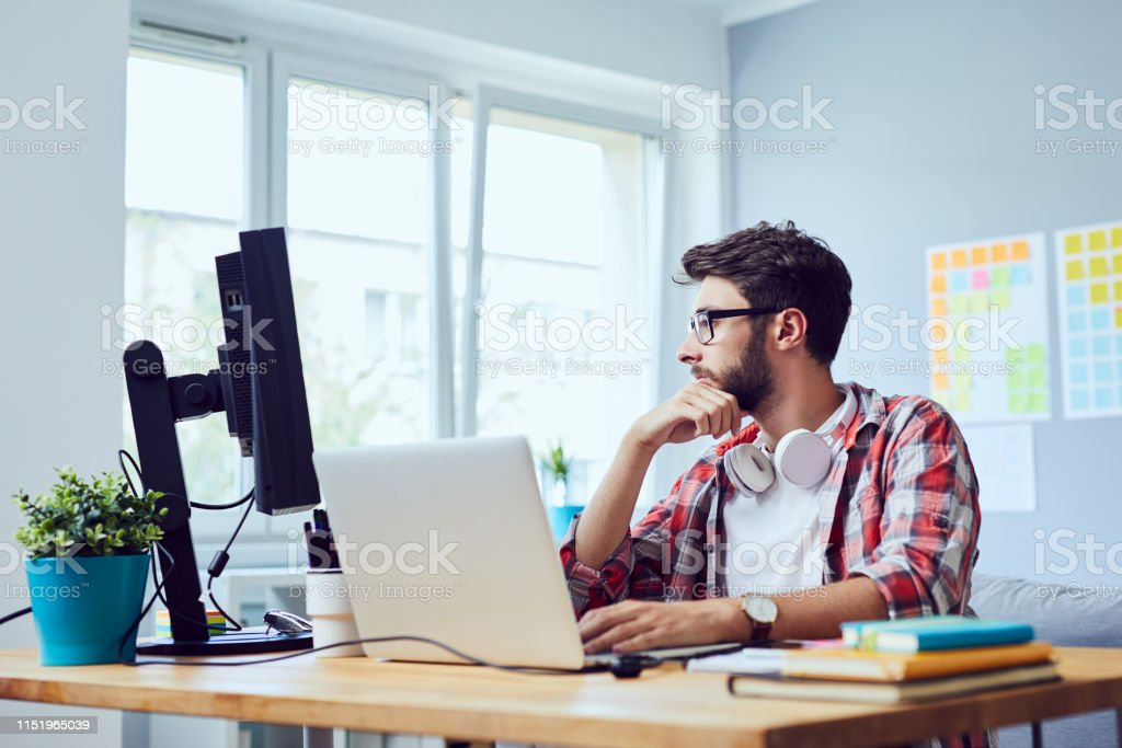 Focused young man thinking about his start-up business while looking at screen in home office Focused young man thinking about his start-up business while looking at screen in home office Adult Stock Photo