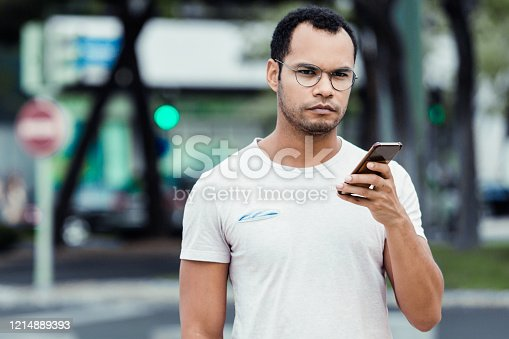 Focused young man walking on street and looking at camera. Handsome African American guy strolling with smartphone. Technology concept