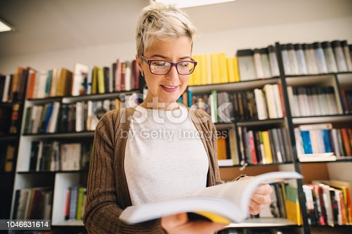 istock Focused young student girl standing in library in front of book shelf and looking at book. Searching for literature for her exam. 1046631614