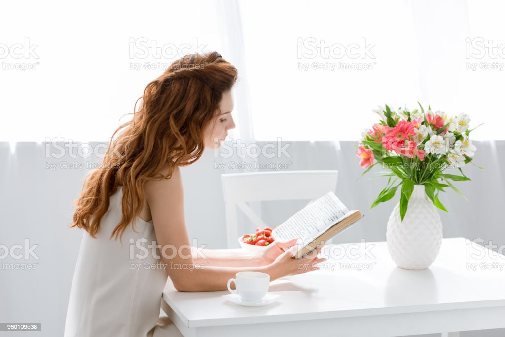 focused young woman reading book while sitting at table with coffee cup and flowers in vase stock photo