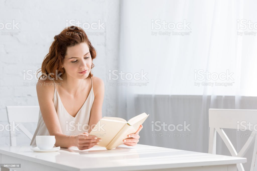 focused young woman reading book with coffee cup on table at home stock photo