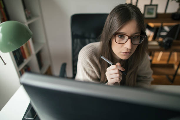 Focused young woman working on desktop stock photo