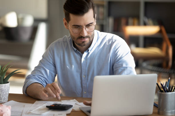 Focuses man calculate expenses pay bills online stock photo