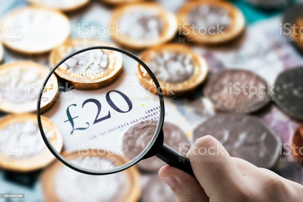 Focusing on money - Magnifying glass over British pound notes. stock photo