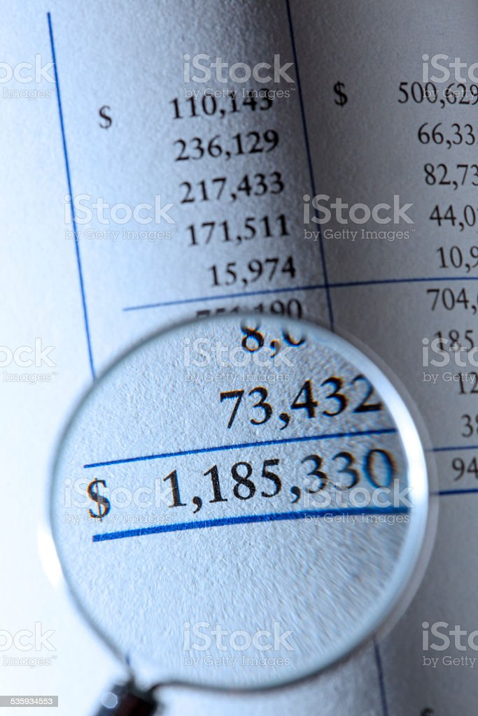 A magnifying glass is focused on the bottom line of a financial...