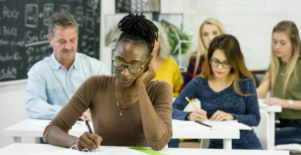 Focusing A group of adult students are sitting at individual desks with papers and books in front of them. They are holding pens and pencils, and are writing down notes adult learning stock pictures, royalty-free photos & images