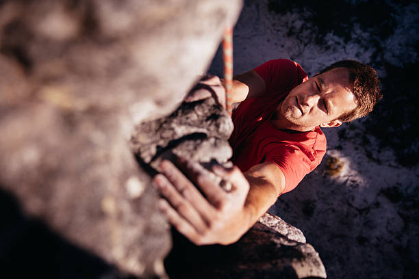 focussed rock climber holding on grip while hanging from boulder - clambering stock photos and pictures