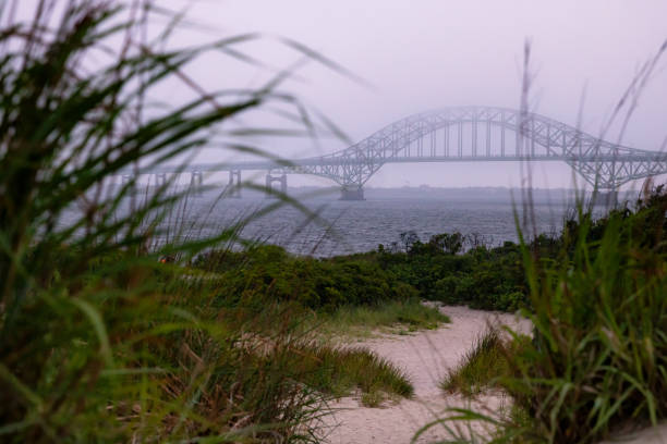 Fog and cloud cover moving in over a steel tied arch bridge and coastal seascape. Fire Island Inlet Bridge - Long Island New York.
