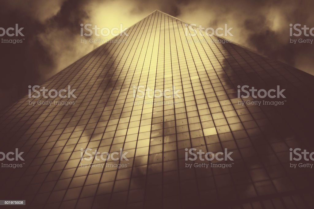 Fog and cloud surround glass skyscraper. Sepia. NYC. stock photo