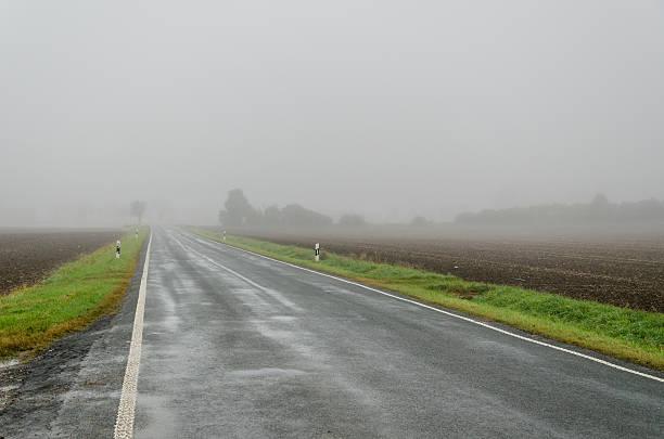 fog and rainy morning at country street- bad november weather - deutsche wetter stock-fotos und bilder