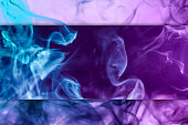 Abstract art colored pink and blue  smoke on black and white isolated background. Stop the movement of multicolored smoke on dark background