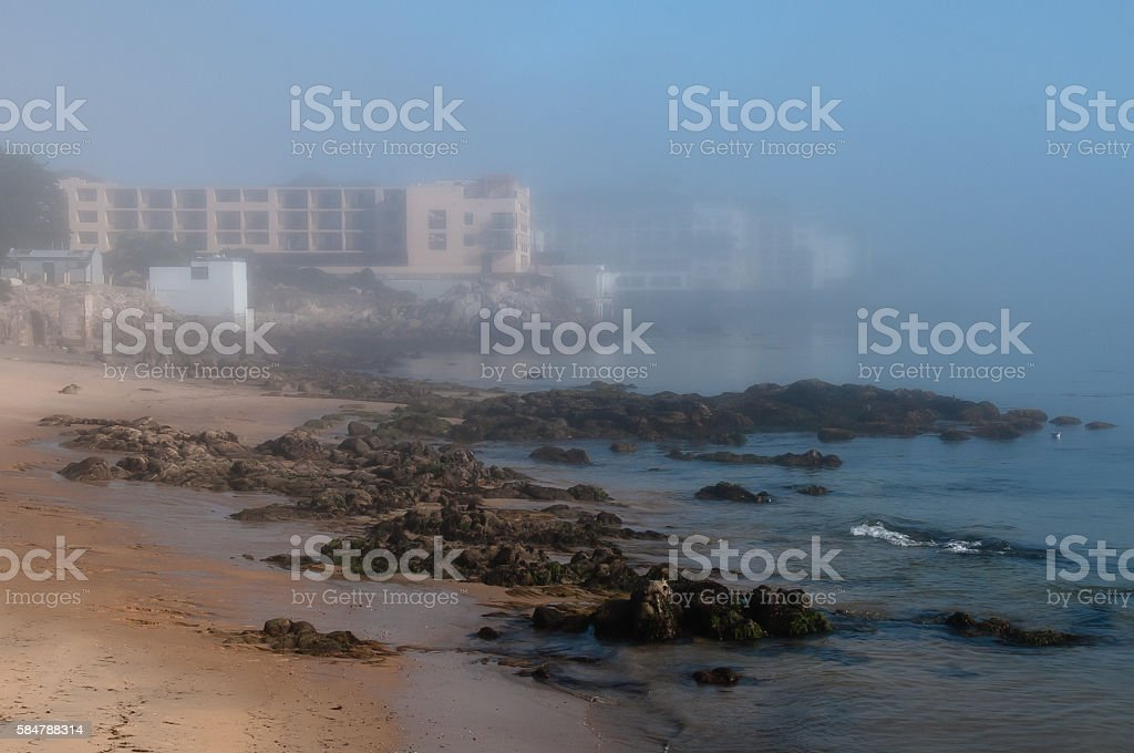 Fog hides cannery row with beach in foreground, horizontal stock photo