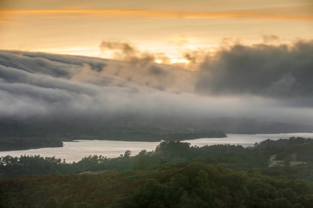 Fog Rolling over Crystal Springs Reservoir as seen from a vista point off Highway 280 on a Summer Sunset. stock photo