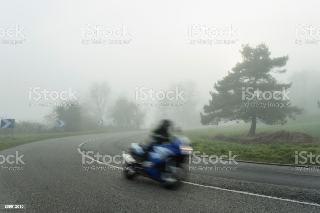 Foggy asphalt curved road with bike passing through the forest. Weather with low visibility in the region of Normandy, France. Country landscape on misty day. Toned stock photo
