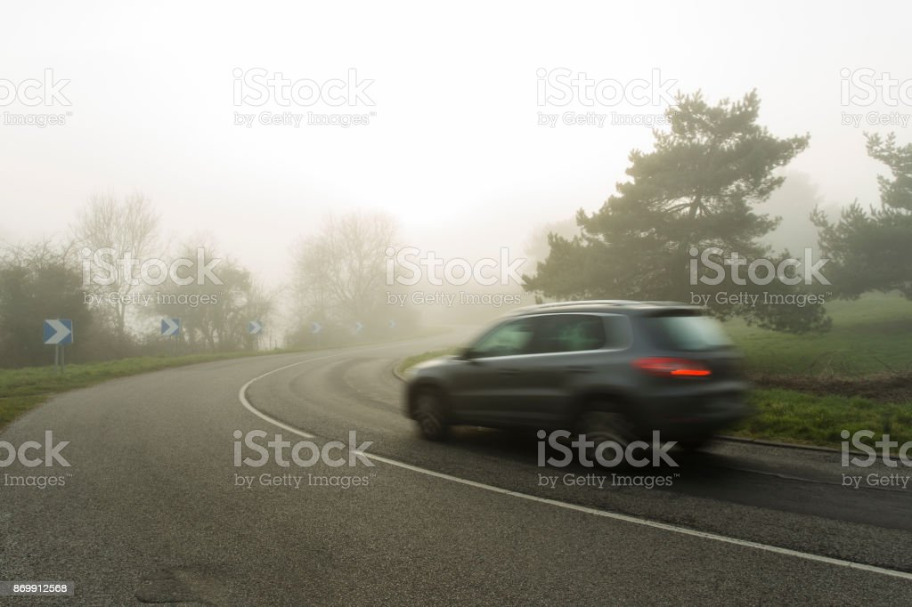 Foggy asphalt curved road with cars passing through the forest. Weather with low visibility in the region of Normandy, France. Country landscape on misty day. Toned stock photo