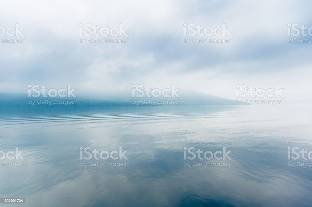 foggy blue lake stock photo