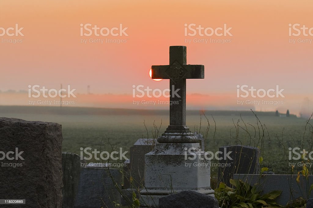 Foggy Cemetary Sunrise and Marble Cross stock photo