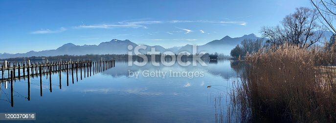 istock Foggy day on Chiemsee Lake in Bavaria - hut and mountains reflecting in water 1200370616