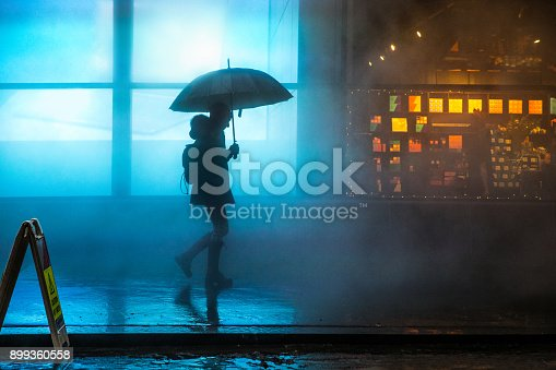Foggy downtown in Lower Manhattan a woman walking under the rain in the dark