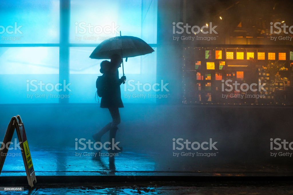Foggy downtown in Lower Manhattan a woman walking under the rain in the dark stock photo
