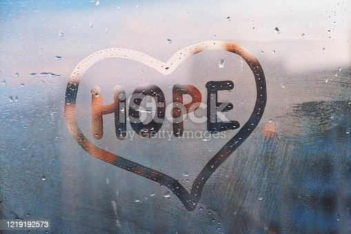 istock Foggy glass on window with written finger word yellow color Hope in paint heart concept photo with copy space on blue and warm background 1219192573