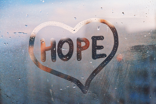 Handwritten word Hope in shape heart on misted glass on window flooded with raindrops on blue cloudy background