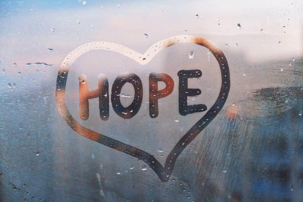 mistig glas op venster met geschreven vingerwoord gele kleur hoop in de foto van het verfhartconcept met exemplaarruimte op blauwe en warme achtergrond - hoop stockfoto's en -beelden