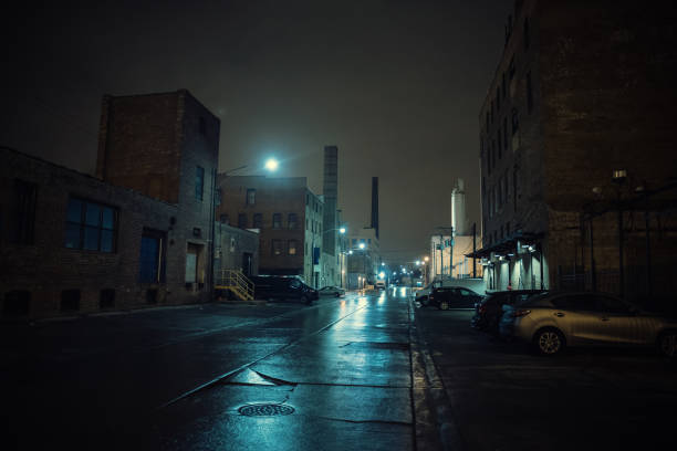 Foggy industrial urban street city night scenery in Chicago with vintage warehouses, factories and smokestacks after a rain. stock photo