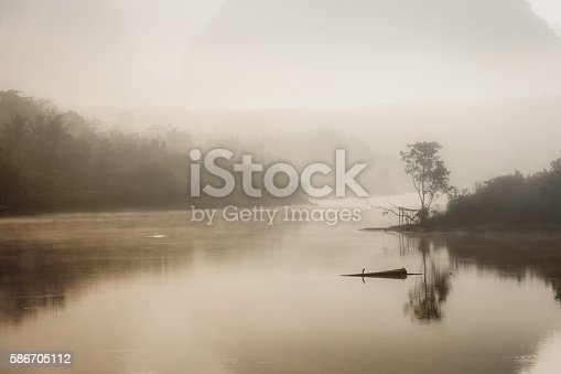 Foggy landscape with a tree silhouette on a fog over lake in morning