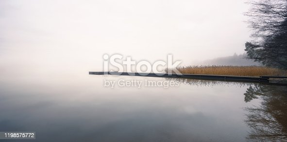 Foggy landscape with calm lake and wooden pier at tranquil autumn morning in Finland