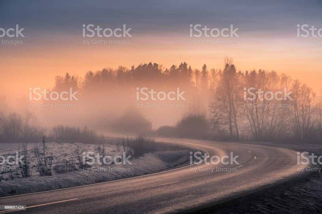 Foggy landscape with road and sunset at evening royalty-free stock photo