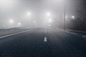 Foggy misty night road illuminated by street lights.
