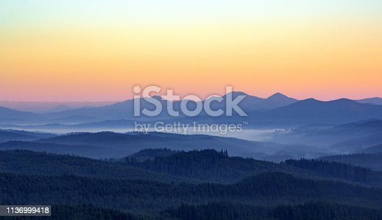 Foggy morning in the mountains with silhouettes of hills. Serenity sunrise with soft sunlight and layers of haze. Mountain landscape with mist in woodland in pastel colors