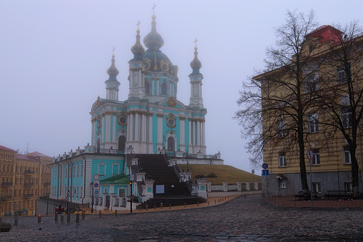 Foggy morning landscape view of ancient baroque Saint Andrew's Church in the Andriyivskyy Uzviz. Mysterious cityscape of Kyiv. Famous touristic place and travel destination.UNESCO world heritage site.