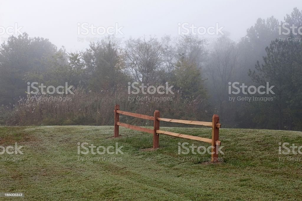 Foggy Morning on grassy hill with Fence stock photo