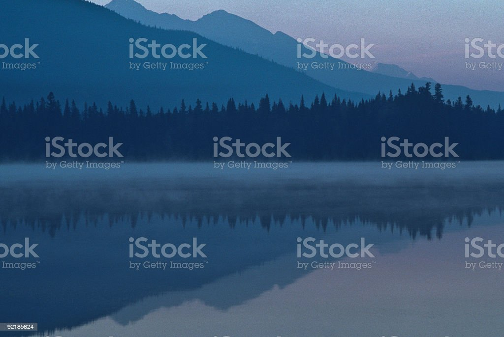Foggy Mountains and Reflections in a Lake stock photo