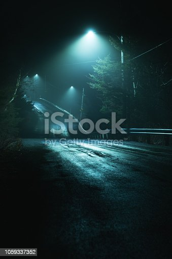 A dirt road is illuminated by a series of street lights on a moody foggy night.