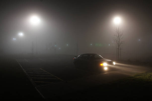 foggy parking lot - mist donker auto stockfoto's en -beelden