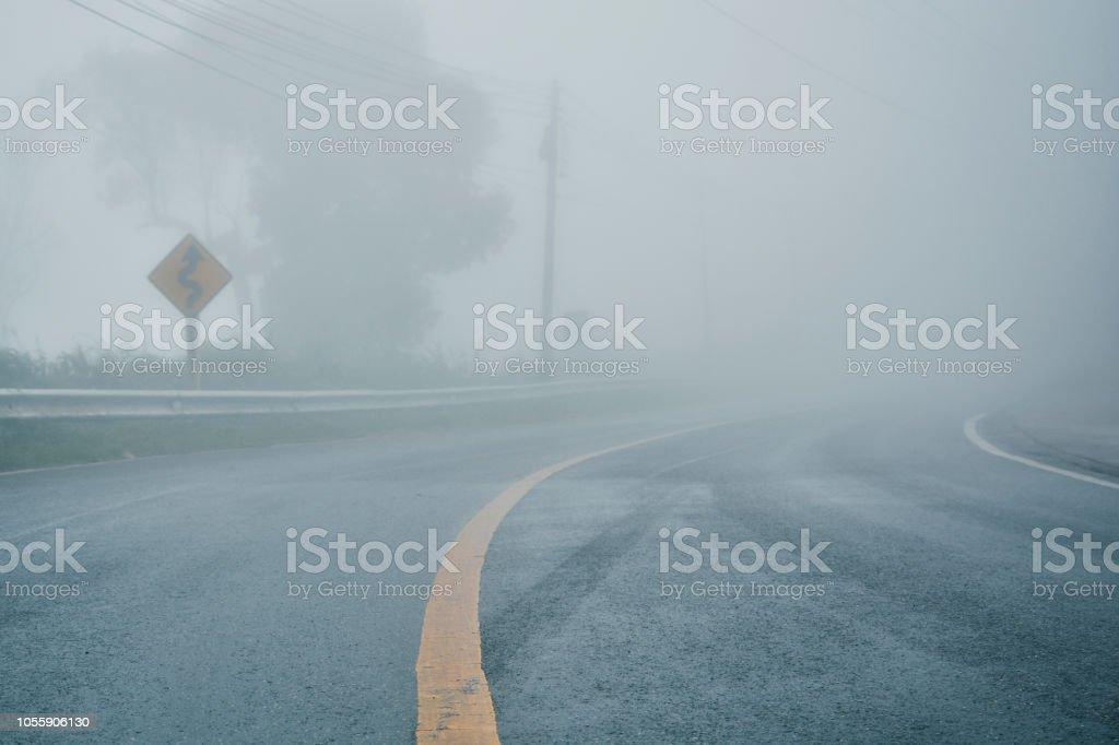 perspectiva de estrada de asfalto rural nebuloso com linha branca, enevoada, estrada, estrada com tráfego e pesado nevoeiro, mau tempo dirigindo foto de stock royalty-free