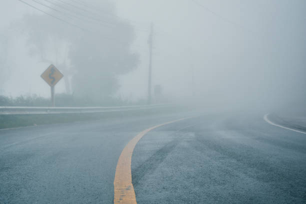 foggy rural asphalt highway perspective with white line, misty road, road with traffic and heavy fog, bad weather driving - fog stock pictures, royalty-free photos & images