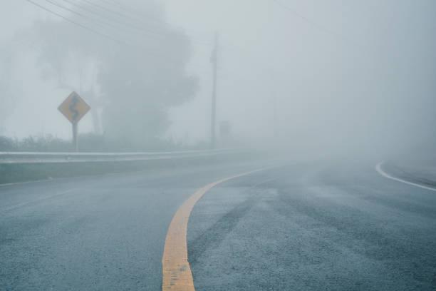 mistige landelijke asfalt snelweg perspectief met witte lijn, mistige weg, weg met verkeer en zware mist, slecht weer rijden - mist stockfoto's en -beelden