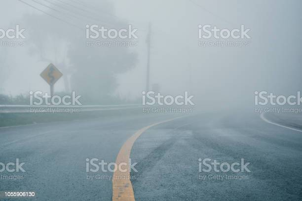 Photo of foggy rural asphalt highway perspective with white line, misty road, Road with traffic and heavy fog, bad weather driving