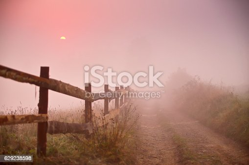 Rustic fence. Fence and dirt road at foggy morning. Misty rural scene