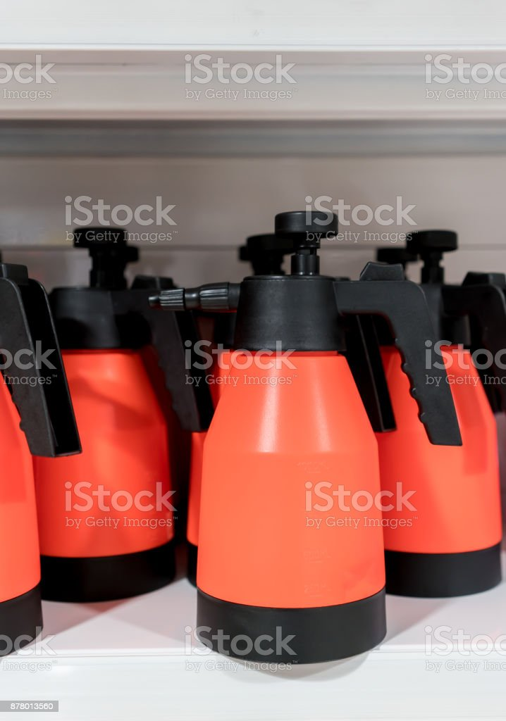 Foggy spray plastic bottles in red and black color on white shelf. Equipment for multipurpose cleaning. stock photo