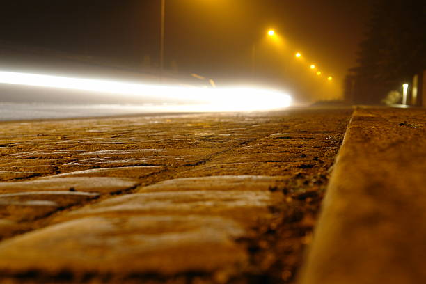 Foggy street at night with car driving by. stock photo